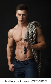 Portrait of a handsome young man with great physique with rope on his shoulder over black background
