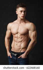 Portrait of a handsome young man with great physique over black background