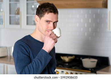 Portrait of handsome young man, guy is standing at kitchen in the morning in pyjama and drinking hot coffee to tea from white mag and looking at camera at home. Caffeine addiction.