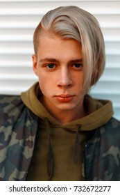 Portrait of a handsome young man with hair in a military jacket with a hood