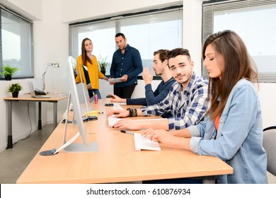 portrait of a handsome young man in high school classroom working in computer on row with teacher and classmates in background