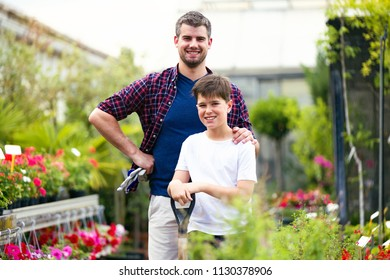 Portrait of handsome young man with his son looking at camera in the greenhouse.