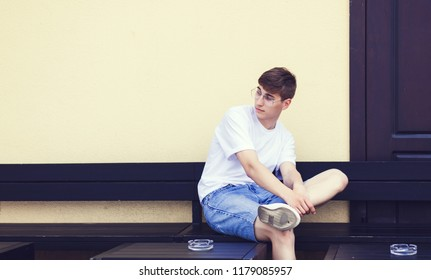 Portrait of a handsome young man in jeans shorts and white t-shirt