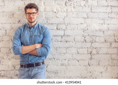 Portrait of handsome young man in jeans clothes and eyeglasses looking at camera and smiling, standing against white brick wall