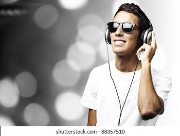 portrait of a handsome young man listening to music against a abstract background