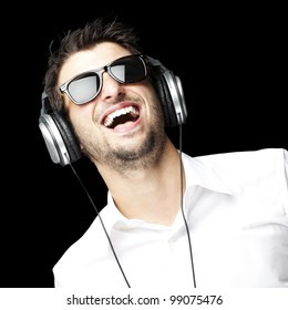 portrait of a handsome young man listening to music with headphones over black background