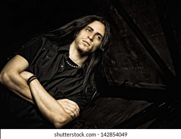 Portrait of a handsome young man with long hair. Low key