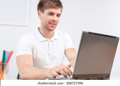 Portrait of a handsome young man looking at the laptop and typing on keyboard, sitting in a light room wearing a white polo shirt, selective focus