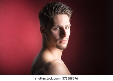 Portrait of a handsome young man looking into camera red background