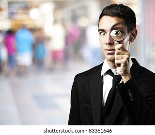portrait of handsome young man with magnifying glass in a shopping center