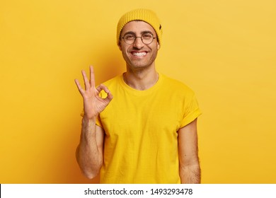 Portrait of handsome young man makes okay gesture, demonstrates agreement, likes idea, smiles happily, wears optical glasses, yellow hat and t shirt, models indoor. Its fine, thank you. Hand sign