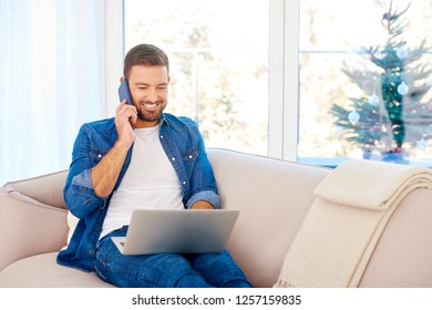 Portrait of handsome young man making a call and using his laptop while sitting on sofa at home.