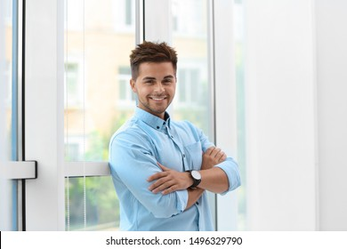 Portrait of handsome young man near window
