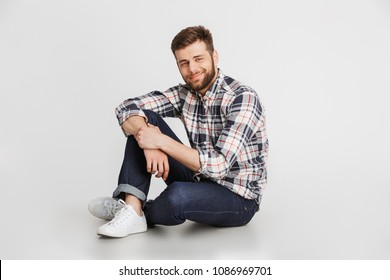 Portrait of a handsome young man in plaid shirt sitting on a floor isolated over white background