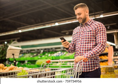 Portrait of handsome young man pushing shopping cart in supermarket and looking at smartphone screen while buying groceries, copy space