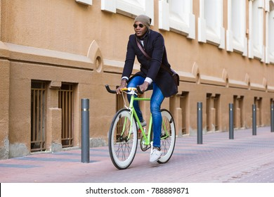 Portrait of handsome young man riding a bike in the street.