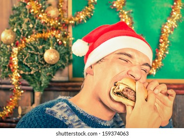 Portrait of an handsome young Man with Santa hat eating Cheeseburger