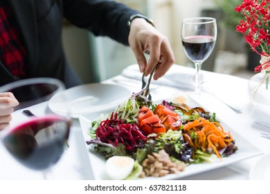 Portrait of handsome young man serving salad on a plate in the restaurant.