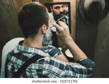 Portrait of handsome young man shaving in vintage interior. Texture effect and film grain add. Not camera noise. Cinematic look. Low Light.