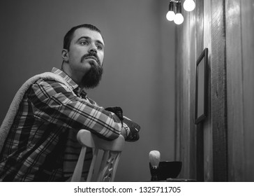 Portrait of handsome young man shaving in vintage interior. Texture effect and film grain add. Not camera noise. Cinematic look. Low Light. Black and white.