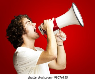 portrait of a handsome young man shouting with megaphone against a red background