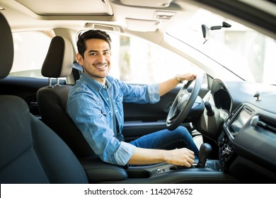 Portrait of handsome young man sitting in the driving seat of his car and making eye contact