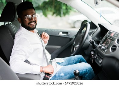 Portrait of handsome young man sitting in driving seat of car and wearing seatbelt for safety