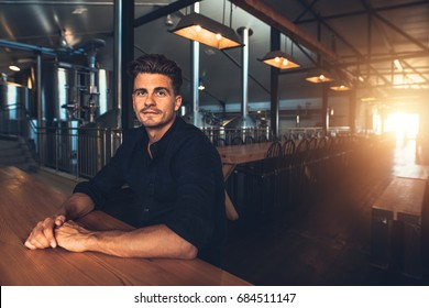 Portrait of handsome young man sitting at table with tanks in background at brewery. Caucasian man at beer tasting area.