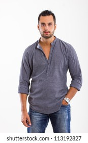Portrait of a handsome young man standing with his hands in pocket against white background.