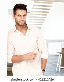 Portrait of handsome young man standing against wall, holding glass of champagne, looking at camera.