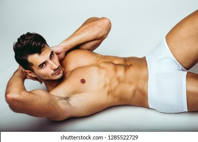 Portrait of handsome young man with stylish haircut in white underwear posing over gray background. Perfect hair & skin. Close up. Studio shot