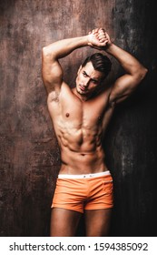 Portrait of handsome young man with stylish haircut in swinwear posing over rusty wall background. Perfect hair & skin. Close up. Studio shot
