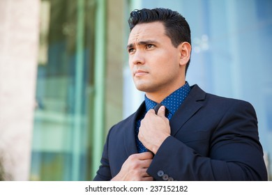 Portrait of a handsome young man in a suit getting ready for an interview and fixing his tie
