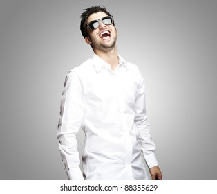 portrait of a handsome young man with sunglasses enjoying over grey background