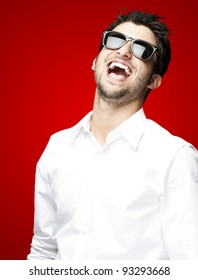 portrait of a handsome young man with sunglasses laughing over a red background