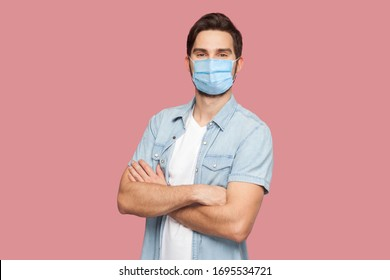 Portrait of handsome young man with surgical medical mask in blue casual style shirt standing, raised arms and looking at camera with smile. indoor studio shot, isolated on pink background.