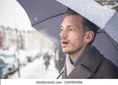 Portrait of a handsome young man with umbrella breathing warm air in winter snow
