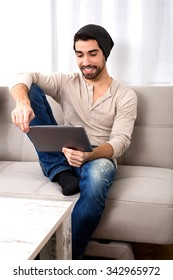 Portrait of a handsome young man using a tablet pc at home