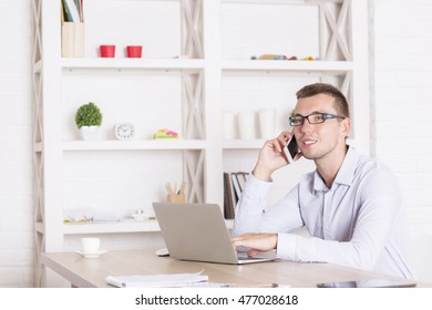 Portrait of handsome young man using laptop computer and talking on phone at wooden desk in modern office interior