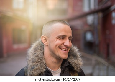 portrait of handsome young man walking on the street and looking at camera