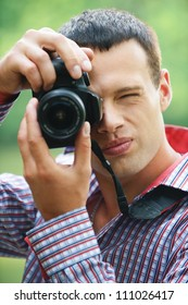 Portrait of handsome young man wearing chequered shirt taking photos at summer green park.
