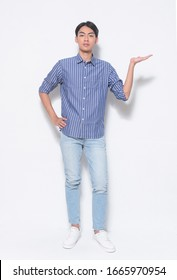 Portrait eines gut aussehenden jungen Mannes mit gestreiftem, langärmelndem Hemd mit lächelndem, fröhlichem Vortrag und Zeiger mit Handfläche einzeln auf weißem Hintergrund