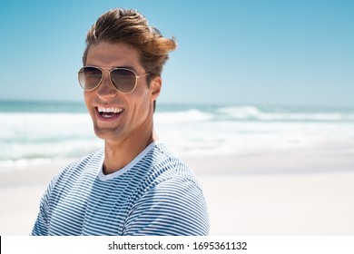 Portrait of handsome young man wearing sunglasses and looking at camera. Portrait of joyful man enjoying summer holiday at beach. Young casual man in shades with big grin and copy space.