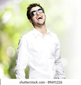 portrait of a handsome young man wearing sunglasses and enjoying against a nature background