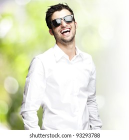 portrait of a handsome young man wearing sunglasses and laughing against a nature background