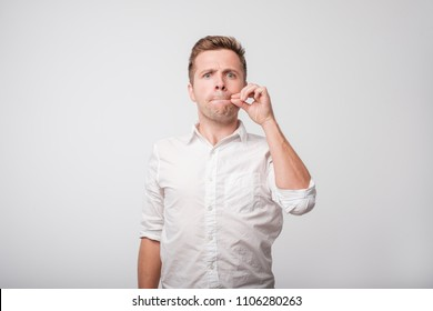 Portrait of handsome young man in white shirt closing his mouth, s he is forced to keep secret, not to tell anyone. concept of confidential information