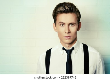 Portrait of a handsome young man in white shirt andblack tie by white brick wall. Business.