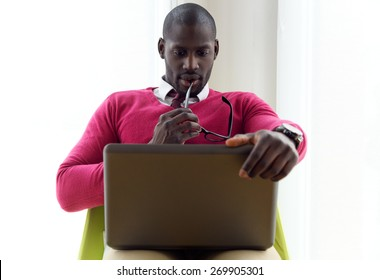 Portrait of handsome young man working with his laptop at home.