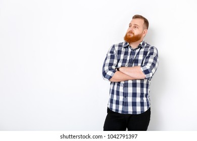portrait of handsome young serious man with red hair and beard in plaid shirt against white wall