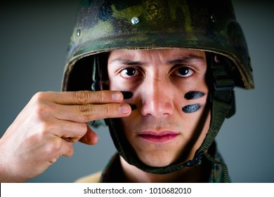 Portrait of handsome young soldier wearing a military uniform, painted his face with two fingers, in a gray background